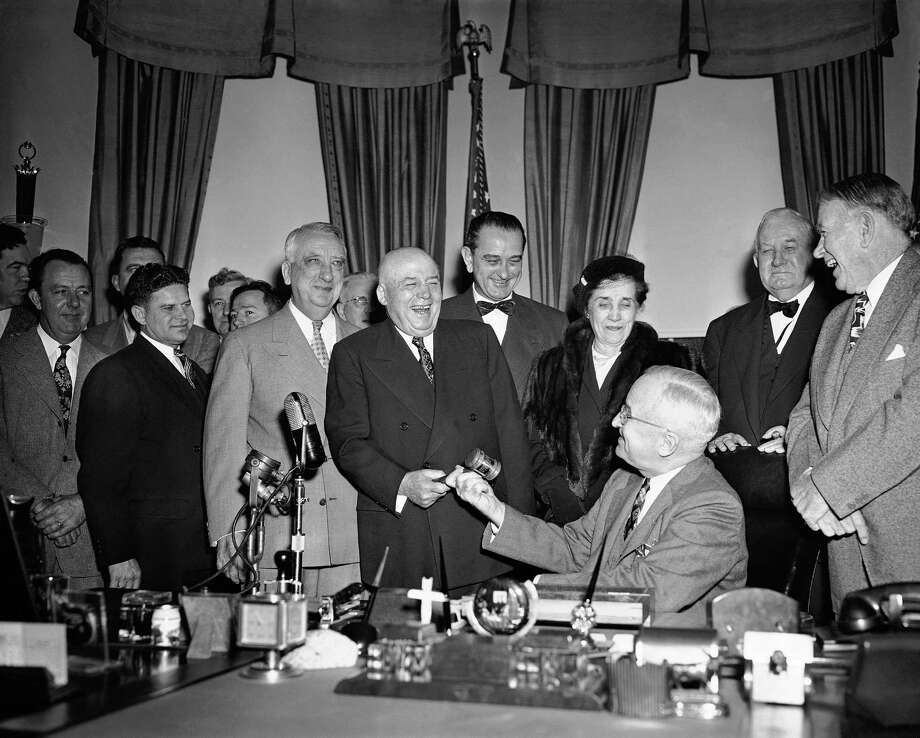 House Speaker Sam Rayburn (D-Tex) (standing left), laughs heartily at the White House in Washington on Jan. 30, 1951 as President Harry Truman gives him a gavel fashioned from timber taken from part of the White House erected in 1817. The ceremony was in honor of Rayburn's breaking on January 30 all time record for tenure of Speaker's chair. Watching are Senator Lyndon Johnson (D-Tex), and Miss Lucinda Rayburn, of Bonham, Texas, the Speaker. (AP Photo/Henry Borroughs ) Photo: Henry Borroughs, STF / AP