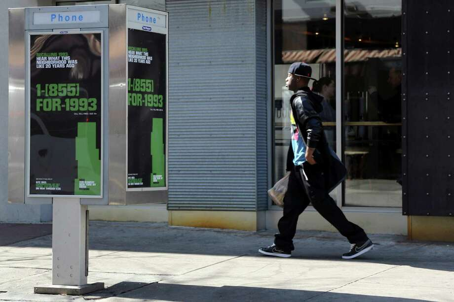 "In this Friday, April 5, 2013 photo, a pedestrian walks past a pay phone advertising the New Museum's ""NYC 1993: Experimental Jet Set, Trash and No Star"" exhibit. The New Museum has launched an exhibit called ""NYC 1993,"" which fills five floors with works by more than 75 different artists. But the interesting part is how they've taken their show to the streets, with 5,000 payphones outfitted with stickers that say ""1-855-FOR-1993."" Photo: Mary Altaffer, AP / AP"