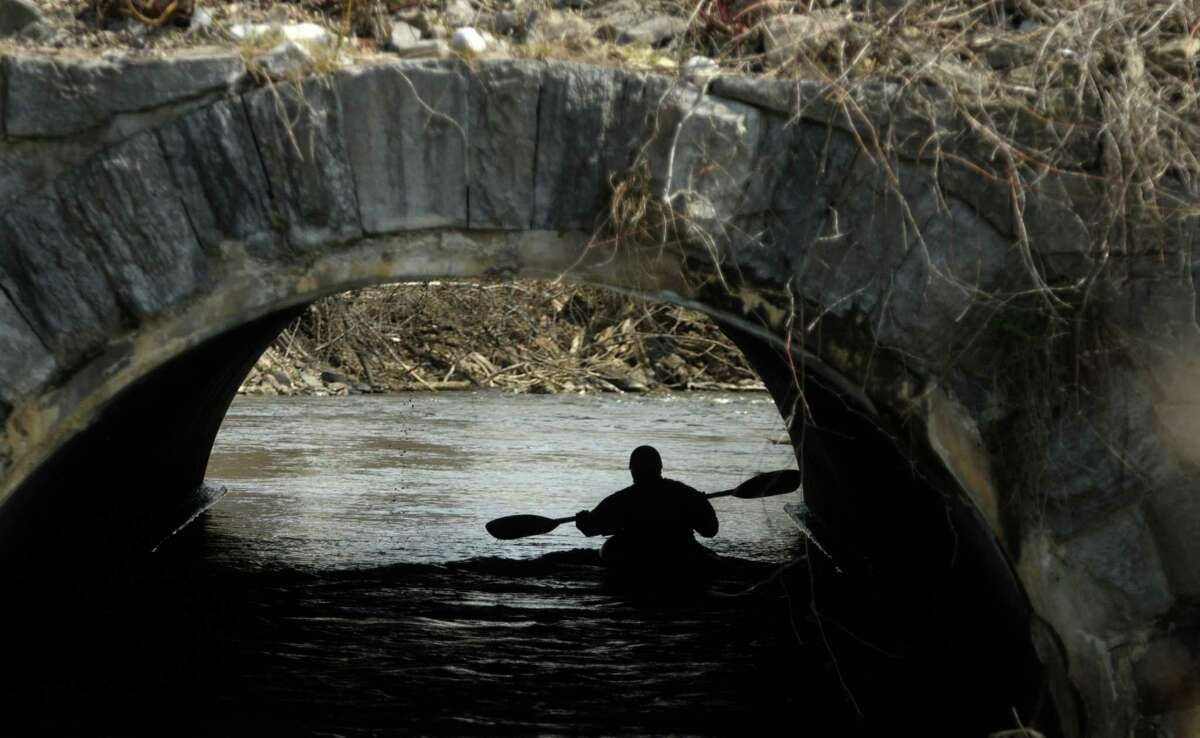 A kayaker goes under the Central Ave. bridge during the 40th running of the Tenandeho Boat Races on Sunday, April 7, 2013 in Mechanicville, NY. The races is open to kayaks, solo canoes, tandem canoes, and polers. Rescue volunteers were positioned after most of the big rapids in the course. (Paul Buckowski / Times Union)