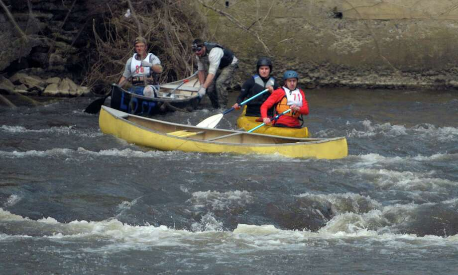 Canoeists try to avoid hitting an empty canoe, after the occupants fell out during the 40th running of the Tenandeho Boat Races on Sunday, April 7, 2013 in Mechanicville, NY.  The races is open to kayaks, solo canoes, tandem canoes, and polers.  Rescue volunteers were positioned after most of the big rapids in the course.   (Paul Buckowski / Times Union) Photo: Paul Buckowski, Albany Times Union / 00021665A