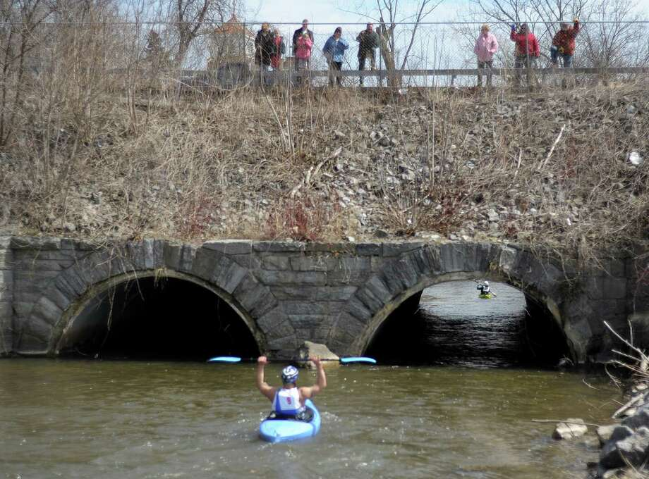 A kayaker acknowledges cheers from the crowd during the 40th running of the Tenandeho Boat Races on Sunday, April 7, 2013 in Mechanicville, NY.  The races is open to kayaks, solo canoes, tandem canoes, and polers.  Rescue volunteers were positioned after most of the big rapids in the course.   (Paul Buckowski / Times Union) Photo: Paul Buckowski, Albany Times Union / 00021665A