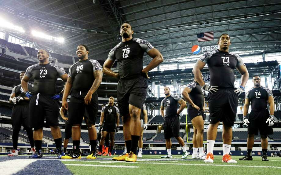 Defensive ends Derren Evans (73), Eric Banford (68), Cameron Henderson (76), Vincent Holmes (77), Frank Beltre (69), Patrick Hampton (75) and John Griggs (74) waits their turn to participate in positions drills during the NFL super regional football combine at Cowboys Stadium, Sunday, April 7, 2013, in Arlington, Texas. (AP Photo/Tony Gutierrez) Photo: Associated Press
