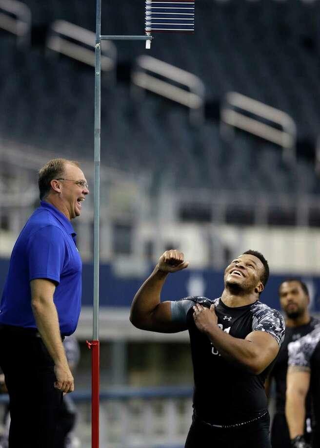 Combine staff member Eric Lougas, left, and British Olympian Lawrence Okoye joke as Okoye prepares for the vertical leap test during the NFL super regional football combine Sunday, April 7, 2013, in Arlington, Texas. (AP Photo/Tony Gutierrez) Photo: Associated Press