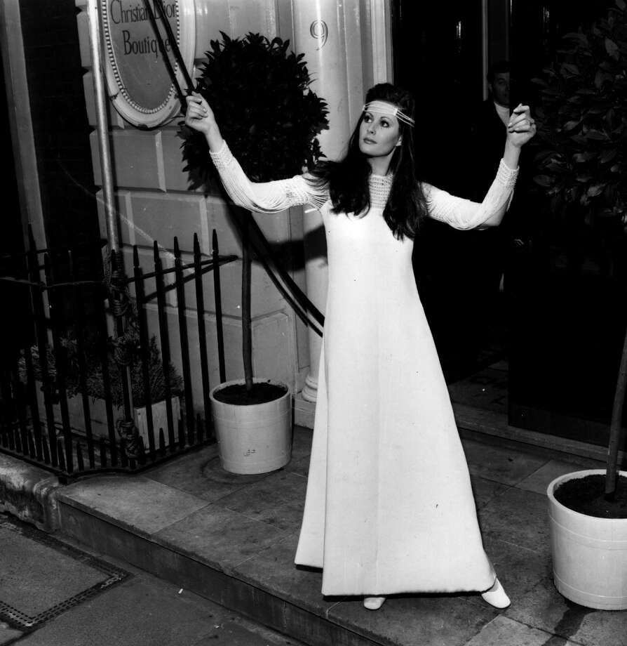 A model wearing a white crepe evening dress with string pearl sleeves, from Christian Dior\'s Spring collection. Photo: Evening Standard, Getty Images / Hulton Archive