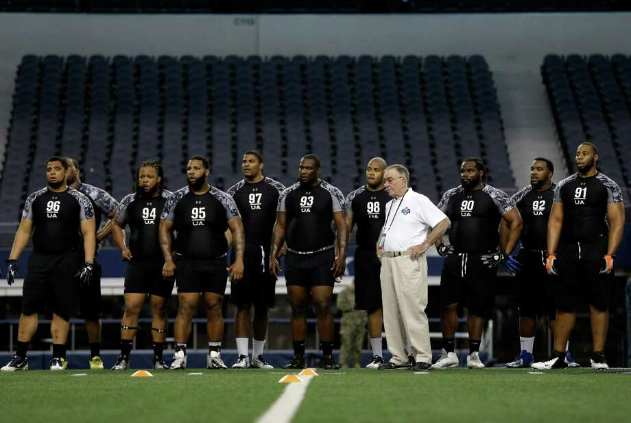 NFL staff member Tom Lovat, center in white, stands with defensive tackles as they prepare for position drill testing during the NFL super regional football combine Sunday, April 7, 2013, in Arlington, Texas. (AP Photo/Tony Gutierrez) Photo: Associated Press