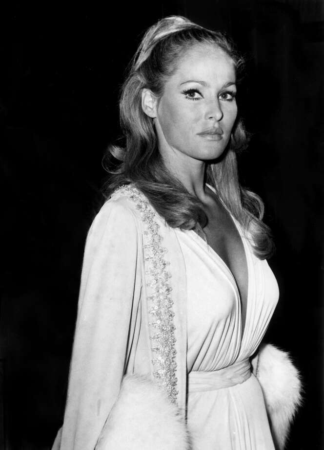 Circa 1965: Swiss-born actor Ursula Andress at an event, wearing a low-cut white gown and a beaded fur wrap. Photo: Express, Getty Images / Archive Photos