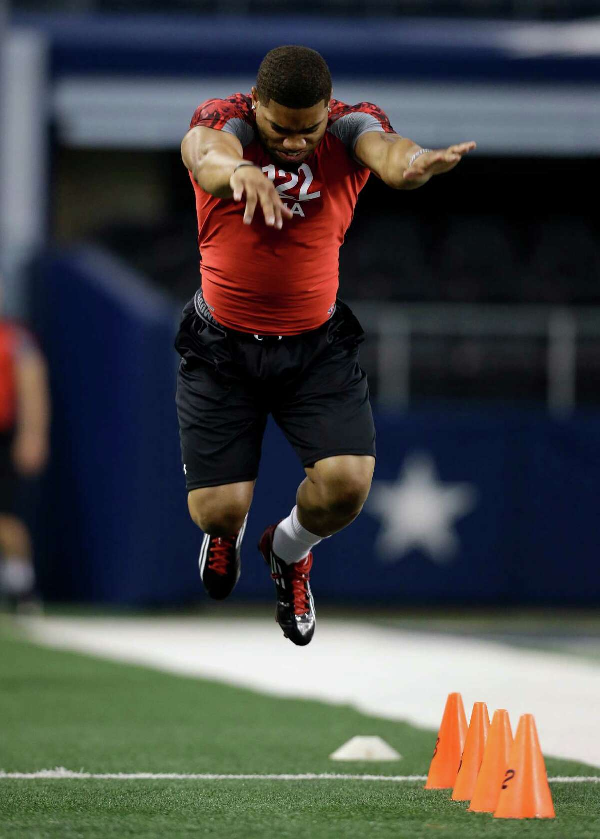 B.J. Daniels leaps forward during the broad jump at the NFL super regional football combine Monday, April 8, 2013, in Arlington, Texas. (AP Photo/Tony Gutierrez)