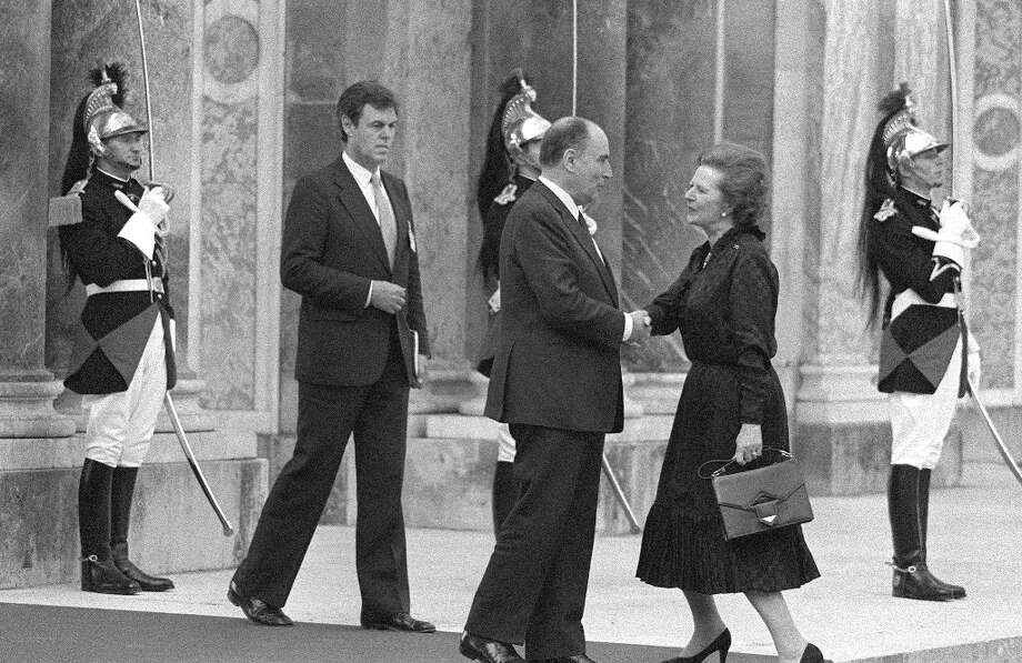 "(FILES) - A picture dated June 4, 1982 shows then French President Francois Mitterrand (C) welcoming British Prime Minister Margaret Thatcher at Grand Trianon in Versailles, at the beginning of the G8 Summit as Republican Guard stand at attention. Former British prime minister Margaret Thatcher, the ""Iron Lady"" who shaped a generation of British politics, died following a stroke on April 8, 2013 at the age of 87, her spokesman said. AFP PHOTO/FILES-/AFP/Getty Images Photo: -, AFP/Getty Images / AFP"