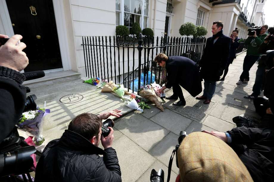 LONDON, ENGLAND - APRIL 08:  A man leaves a book next to floral tributes outside the residence of Baroness Thatcher in Chester Square in front of photographers and members of the media on April 8, 2013 in London, England. It has been confirmed that Lady Thatcher has died this morning following a stroke aged 87. Margaret Thatcher was the first female British Prime Minster and governed the UK from 1979  to 1990. She led the UK through some turbulent years and contentious issues including the Falklands War, the miner's strike and the Poll Tax riots. Photo: Peter Macdiarmid, Getty Images / 2013 Getty Images