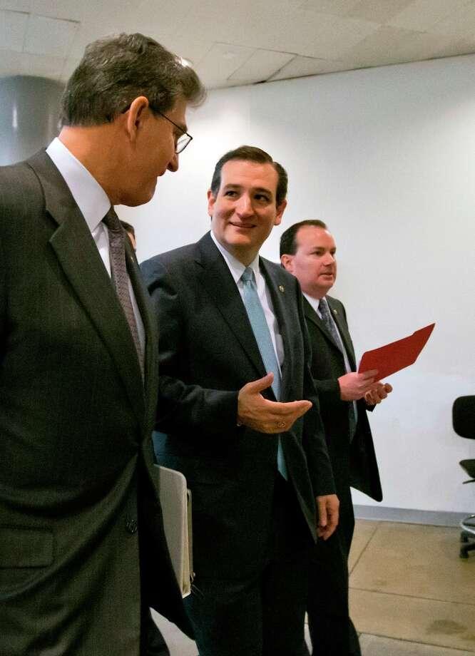From left, Sen. Joe Manchin, D-W.Va., Sen. Ted Cruz, R-Texas, and Sen. Mike Lee, R-Utah, head to the Senate floor to vote on amendments to the budget resolution, at the Capitol in Washington, Friday, March 22, 2013. (AP Photo/J. Scott Applewhite) Photo: J. Scott Applewhite, Associated Press