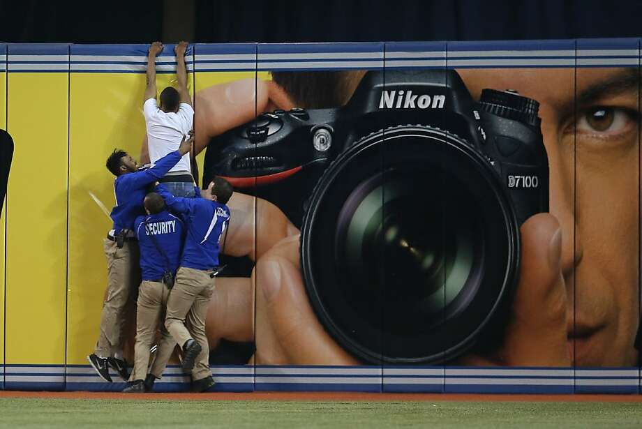 Catch of the game:A baseball-interrupting yahoo tries to climb the outfield wall of the Rogers Centre in Toronto, but security guards pull him down. Photo: Tom Szczerbowski, Getty Images
