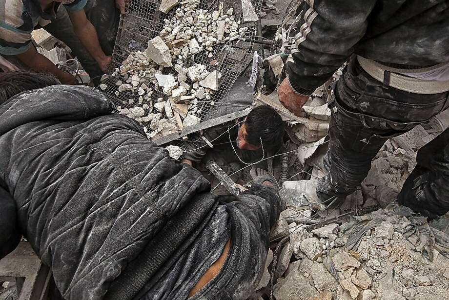 TOPSHOTS Syrians try to free a man trapped under the rubble following an air strike by government forces on April 7, 2013 that destroyed two five-storey apartment blocks and severely damaged ten buildings in a residential neighbourhood of the northern Syrian city of Aleppo, according to eyewitnesses. Warplanes also raided Yabrud near Damascus and Qusayr in the central province of Homs, as tanks shelled rebel enclaves in Homs city the same day.  AFP PHOTO / VICTOR BREINERVICTOR BREINER/AFP/Getty Images Photo: Victor Breiner, AFP/Getty Images