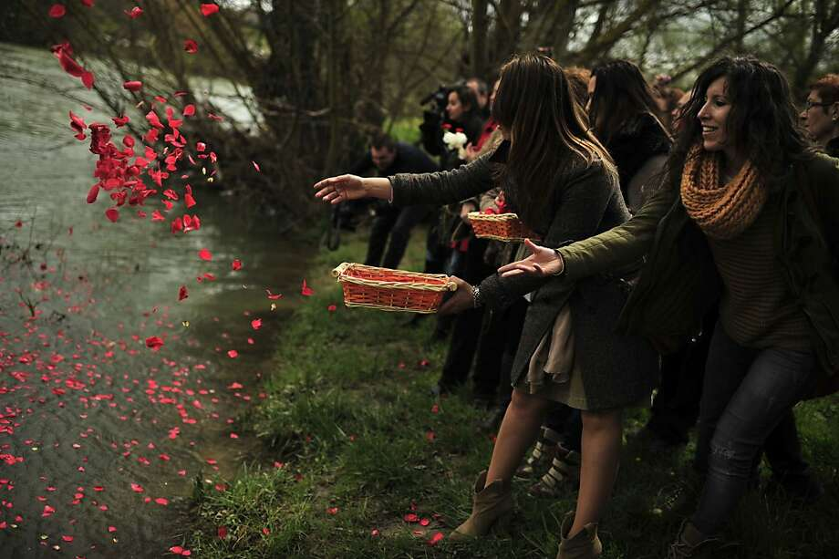 Female gypsy people throw flower petals into the Arga River in honor of their ancestors on the Day of the Gypsy, in Pamplona northern Spain, on Monday, April 8, 2013.(AP Photo/Alvaro Barrientos) Photo: Alvaro Barrientos, Associated Press