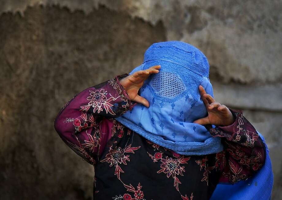 An Afghan girl tries to peer through the holes of her burqa as she plays with other children in the old town of Kabul, Afghanistan, Sunday, April 7, 2013. (AP Photo/Anja Niedringhaus) Photo: Anja Niedringhaus, Associated Press