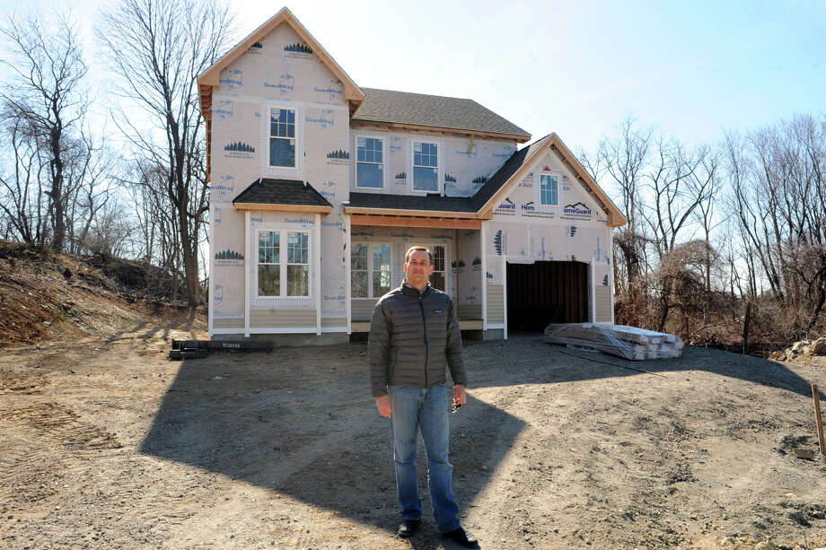 Bryan Robik, managing member of RG Building & Development, stands in front of the first house under construction in Clinton Avenue Estates, in Stratford, Conn. April 4th, 2013. Photo: Ned Gerard / Connecticut Post