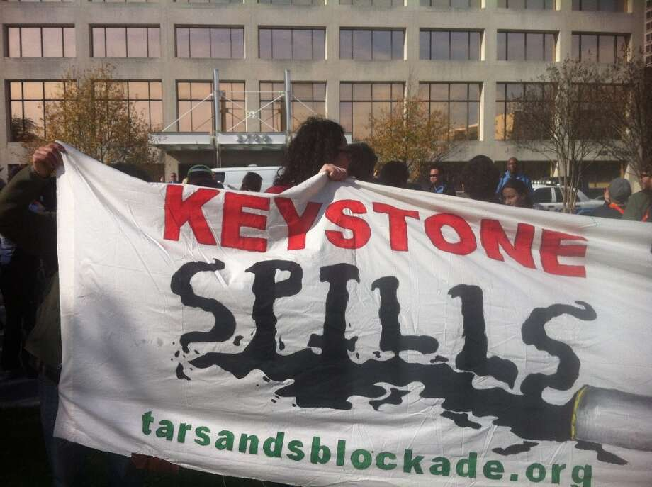 Scores of Keystone XL Pipeline protesters, led by the Tar Sands Blockade, protested oustide one of TransCanada's Houston offices. Photo: Cody Duty, Houston Chronicle