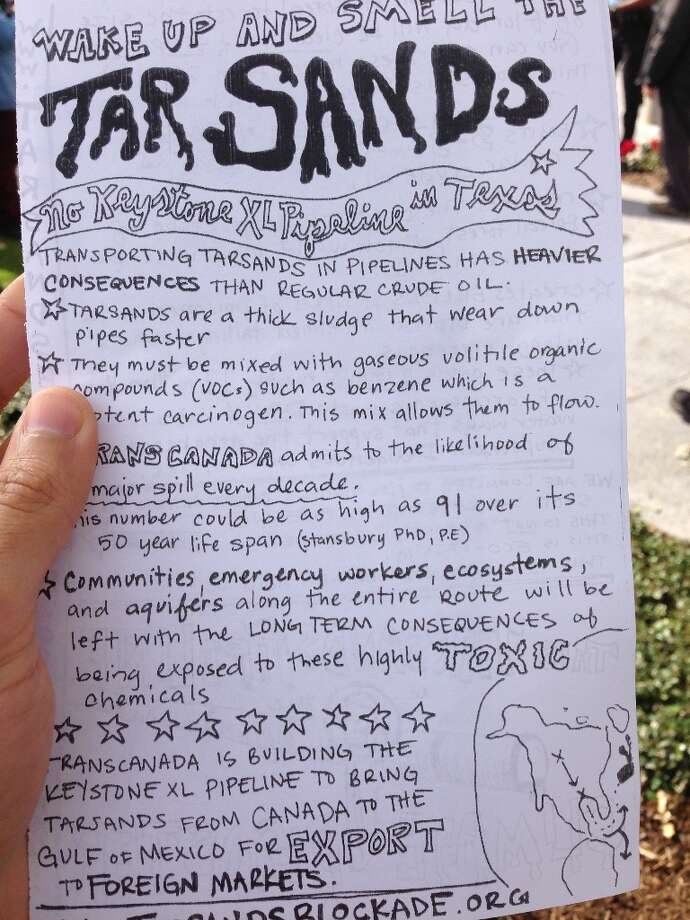 Protesters distributed a flier to shoppers and other passers by detailing their arguments against the Keystone XL pipeline. Photo: Zain Shauk/Houston Chronicle