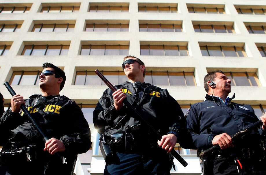 Police stand in front of an office building in the 2700 block of Post Oak Blvd., whose lobby protesters occupied to oppose the Keystone XL Pipeline. Photo: Cody Duty/Houston Chronicle, © 2012 Houston Chronicle / © 2012 Houston Chronicle