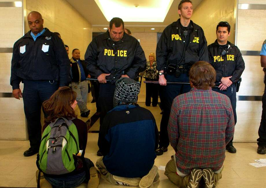 Protestors sit in the lobby of a building in the 2700 block of Post Oak Blvd., containing an office for Transcanada, owner of the Keystone XL Pipeline. Photo: Cody Duty/Houston Chronicle, Houston Chronicle / © 2012 Houston Chronicle