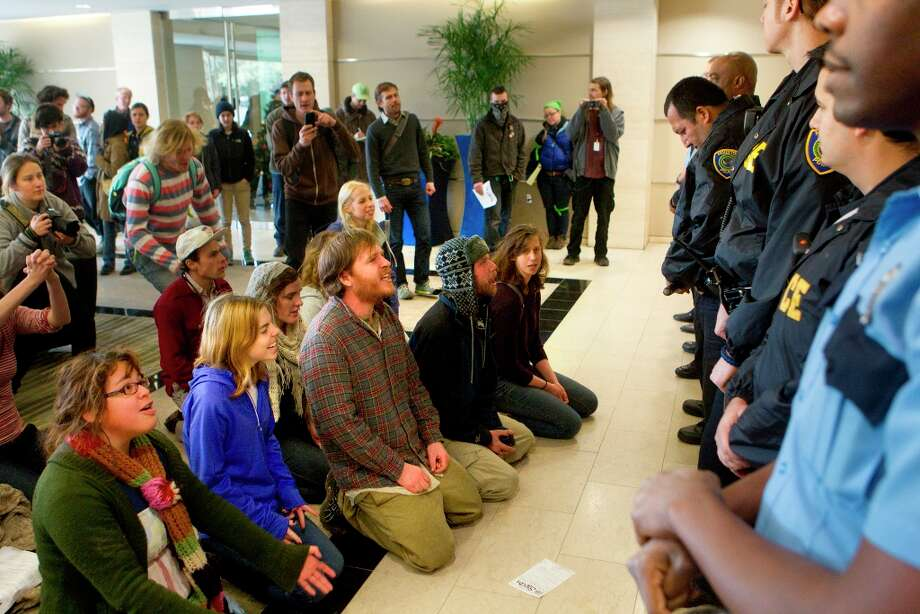 Protestors sit in the lobby of a Houston building containing offices for TransCanada, owner of the Keystone XL Pipeline. Photo: Cody Duty/Houston Chronicle, Houston Chronicle / © 2012 Houston Chronicle