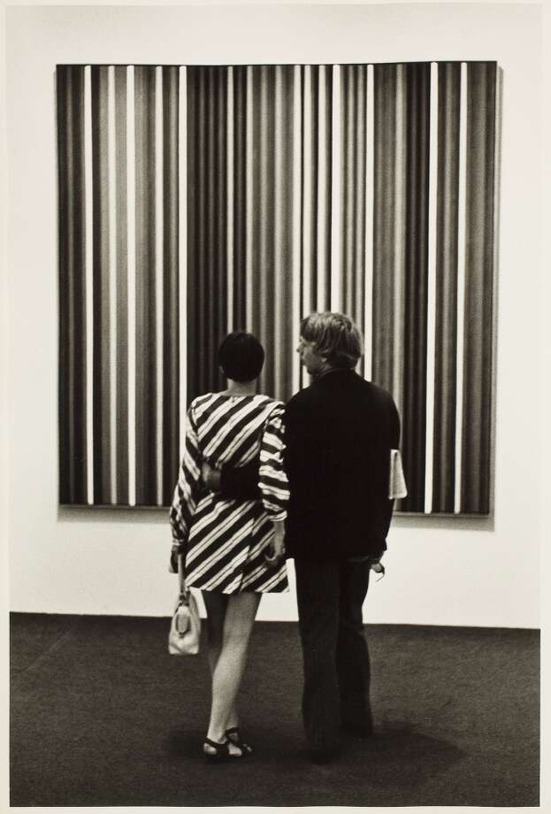 Two visitors, a man and a woman, to the Museum of Modern Art stand and look at a vertically striped painting, New York, New York, 1967. The woman is wearing a diagonally striped dress that contrasts with the vertical stripes of the painting. Photo: George Eastman House, Getty Images / Archive Photos