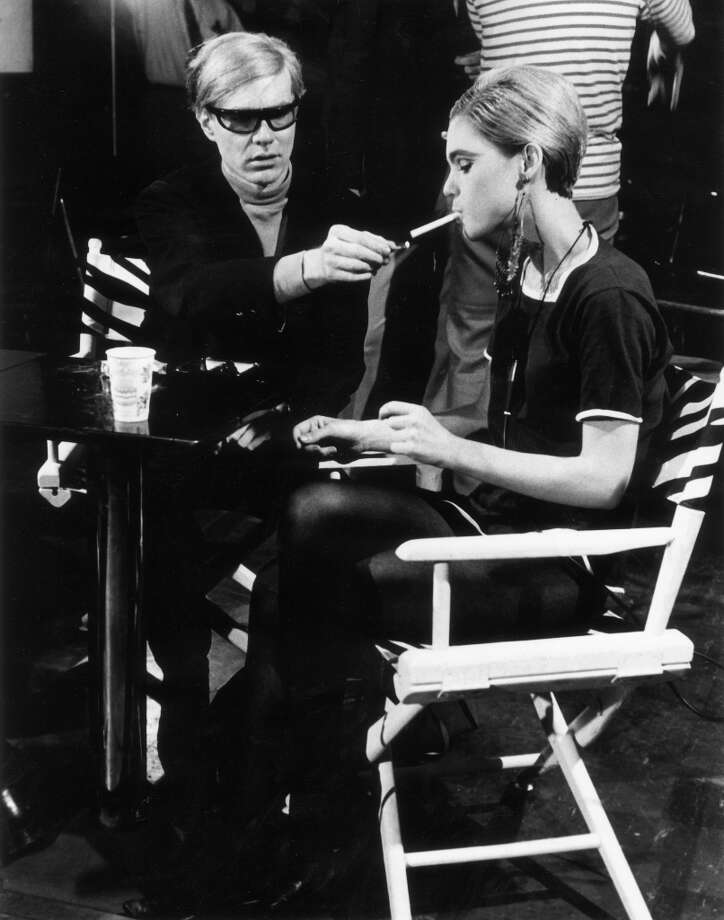 Circa 1965:  American Pop artist Andy Warhol (192-1987) sits next to actor Edie Sedgwick (1943-1971) and lights her cigarette, on the set of one of his films. Photo: Walter Daran, Getty Images / Archive Photos