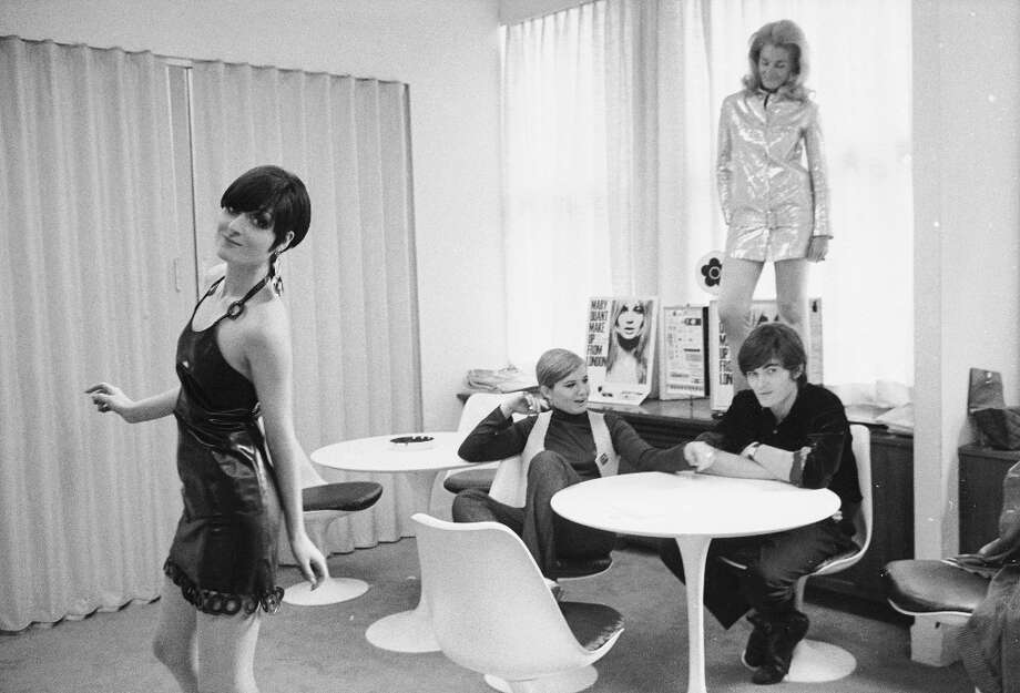 American fashion designer Betsey Johnson (second left) sits with a man at a table and smokes in her studio as one model prances about and poses for pictures and another dances on a windowsill, New York, September 6, 1966. Photo: Susan Wood/Getty Images, Getty Images / 2006 Getty Images