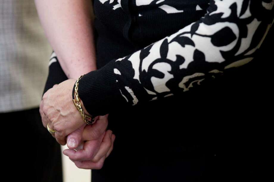 Anne Pardee, left, and her sister Judee Pardee Peterson hold hands following thefuneral for their father, Jack Pardee, the former University of Houston and Houston Oilers head coach, at St. Michael Catholic Church on Monday, April 8, 2013, in Houston. Photo: Brett Coomer, Houston Chronicle / © 2013 Houston Chronicle