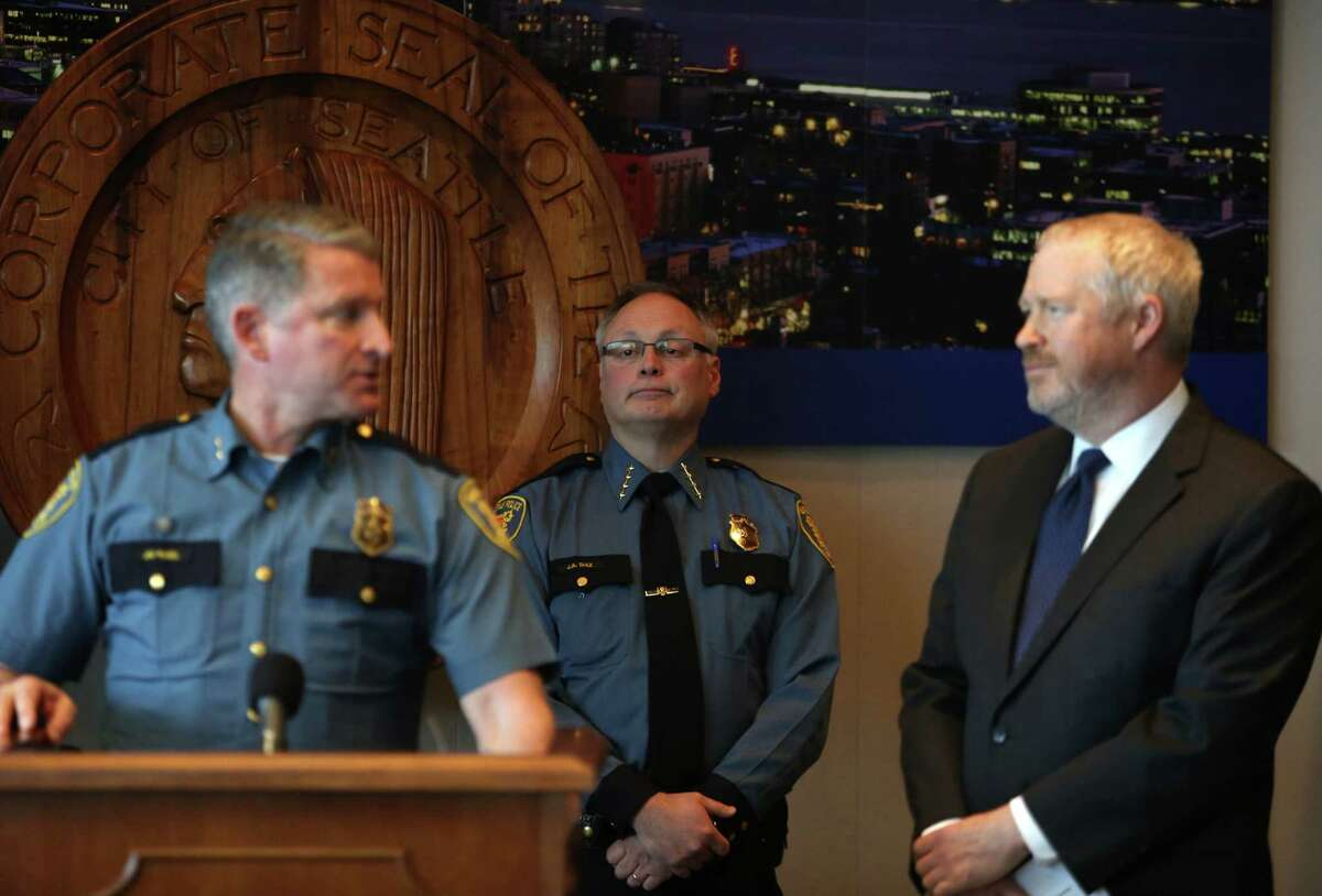 Seattle Police Chief Chief John Diaz, rear, listens as Assistant Chief Jim Pugel and Mayor Mike McGinn address the public during a press conference on Monday, April 8, 2013 at City Hall in Seattle. Diaz announced his retirement and the McGinn appointed Pugel as interim chief.