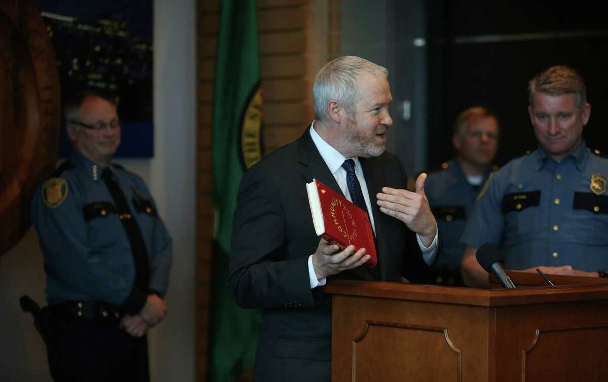 Mayor Mike McGinn holds up a book as he talks about Seattle Police Chief Chief John Diaz, rear left, during a press conference where Diaz announced his retirement on Monday, April 8, 2013 at City Hall in Seattle.