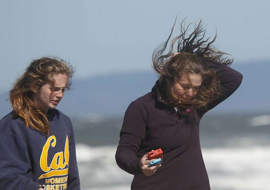 Kira McPolin (right) , 16 holds back her hair as it blows in winds after she and friend Julia Sullivan (left), 16, took photos of themselves in the wind on Ocean Beach as the St. Ignatius sophomores enjoy their last day of Easter break on Monday, April 8, 2013. Photo: Lea Suzuki, The Chronicle