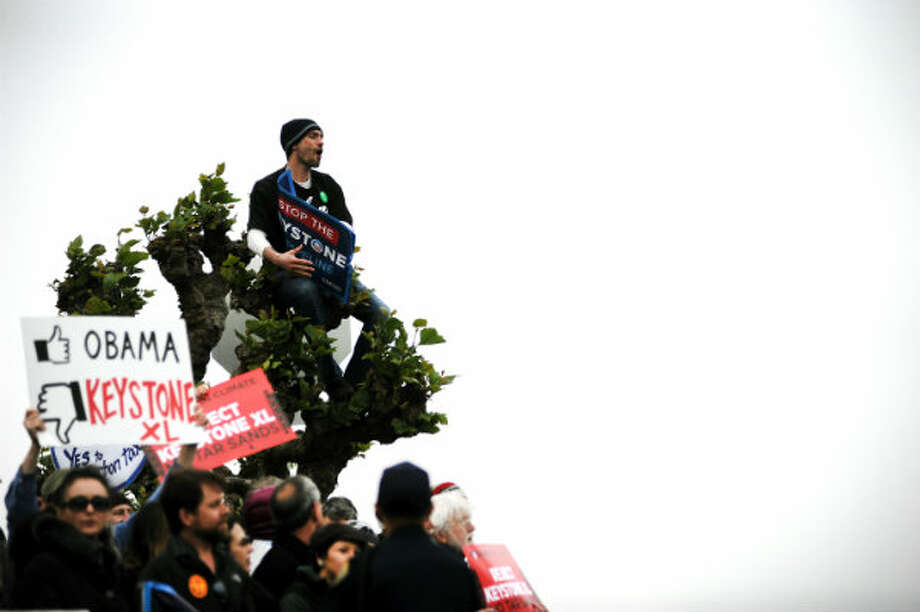 A protestor briefly climbed a tree as he and others gathered at the intersection of Divisadero and Broadway. Protestors gathered in San Francisco, CA Wednesday April 3rd, 2013 to voice their opposition to the Keystone XL Pipeline during a visit by President Obama. Photo: Michael Short, San Francisco Chronicle