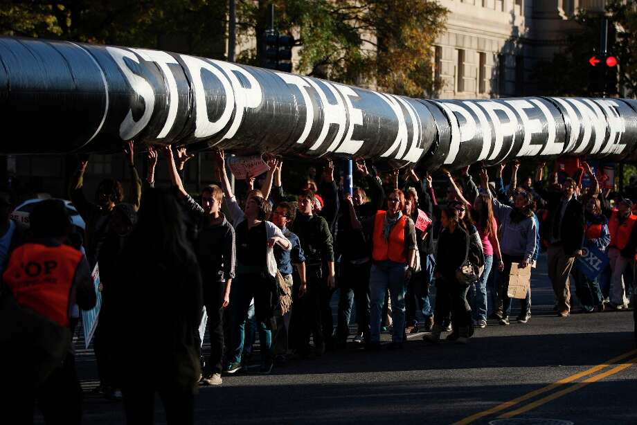 A mock oil pipeline is carried during a Keystone XL tar sands oil pipeline demonstration near the White House in Washington, D.C., U.S., on Sunday, Nov. 6, 2011. Pipeline opponents say extracting crude from sand emits three times more carbon than conventional oil production, contributing to global warming that Obama pledged to fight. They say their protest in Washington reflects public anger at corporate greed. Photo: Andrew Harrer, Bloomberg / © 2011 Bloomberg Finance LP