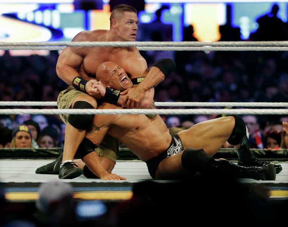 "Wrestler John Cena, top, chokes Dwayne ""The Rock""  Johnson during Sunday's WrestleMania. Cena won the championship match. Photo: Mel Evans, STF / AP"