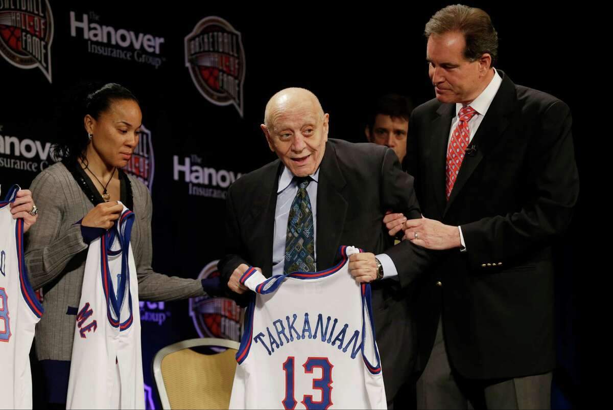 Former UNLV coach Jerry Tarkanian, center, is helped on stage by CBS announcer Jim Nantz, right, during the Naismith Memorial Basketball Hall of Fame class announcement, Monday, April 8, 2013, in Atlanta, Georgia. (AP Photo/Charlie Neibergall)