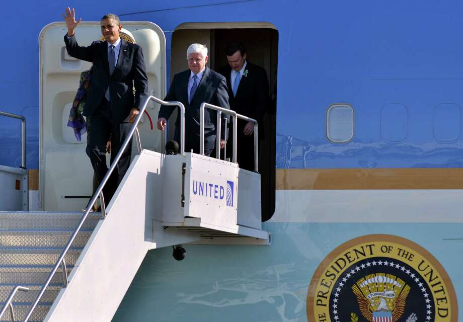 President Barack Obama waves from Air Force One after landing at Bradley Air National Guard Base in East Granby, Conn., Monday, April 8, 2013. Obama arrived for an event scheduled at the University of Hartford where he was to urge lawmakers to act on his proposed gun control legislation. Also seen are, from left, Rep. John Larson, D-CT, and Sen. Chris Murphy, D-CT.  (AP Photo/Josh Reynolds) Photo: AP