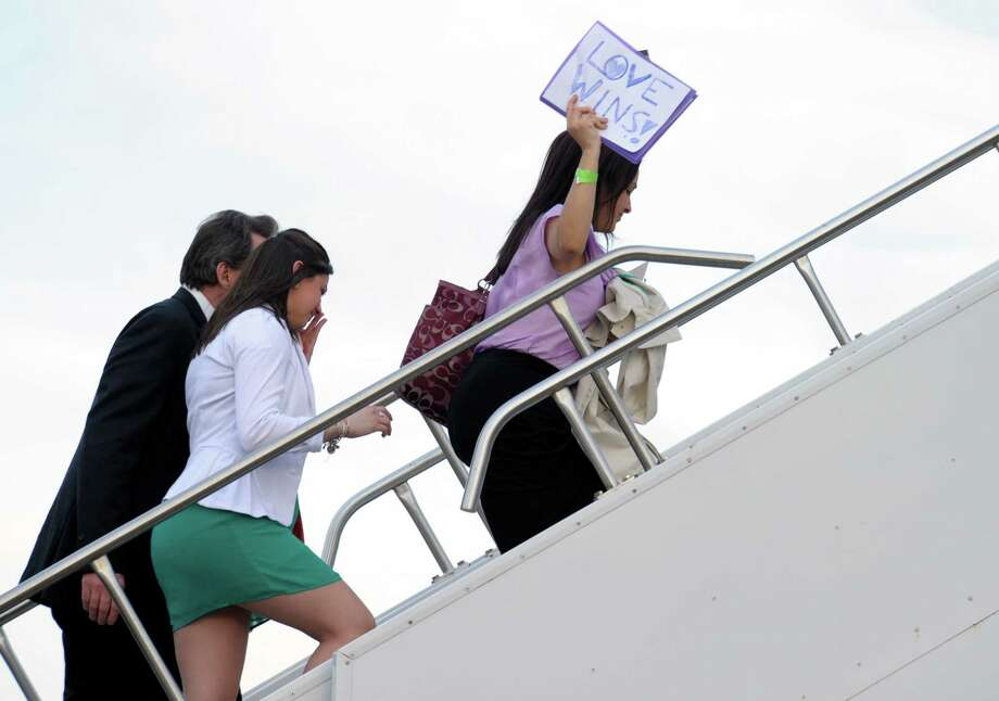Nelba Marquez-Greene, mother of 6-year-old Ana, holds sign as she walks up the steps of Air Force One at Bradley Air Force Base in Conn., Monday, April 8, 2013, with families of those killed in the Sandy Hook Elementary School shooting in Newtown who are returning to Washington with the president. (AP Photo/Susan Walsh) Photo: AP