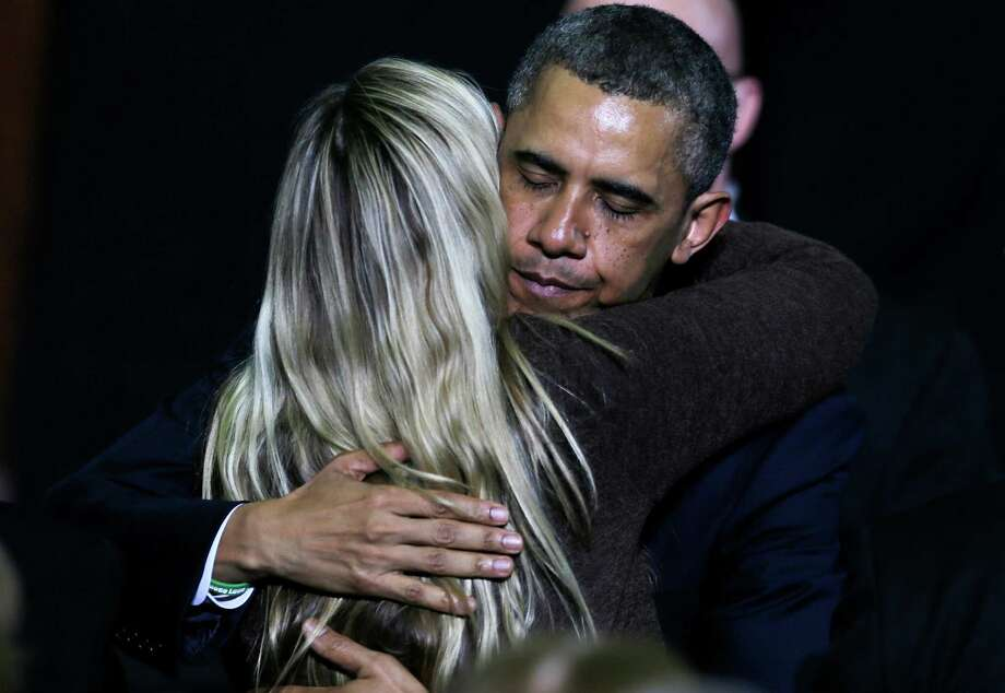 President Obama embraces a woman while honoring shooting victim's families during a visit to the University of Hartford, in Hartford, Conn., Monday, April 8, 2013. The President visited the school to highlight gun control legislation and to meet with the families of victims from the Sandy Hook elementary school shootings.(AP Photo/Charles Krupa) Photo: AP