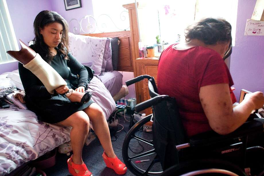 Imani Evans puts a shoe on her mother, Quanikki Van Hook\'s prosthetic leg as they get ready for the funeral of Imani\'s great grandmother Ernestine Shepherd in  El Cerrito, CA Saturday April 6th, 2013. Photo: Michael Short, Special To The Chronicle / ONLINE_YES
