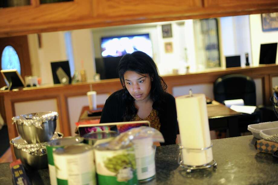 Imani takes a break from cooking to catch up with a few emails for school.  Visiting home from Humboldt State University, Imani Evans helps her disabled mother, Quanikki Van Hook, in the kitchen as they prepare food for the funeral of Imani\'s great grandmother.  In El Cerrito, CA Friday April 5th, 2013. Photo: Michael Short, Special To The Chronicle / ONLINE_YES