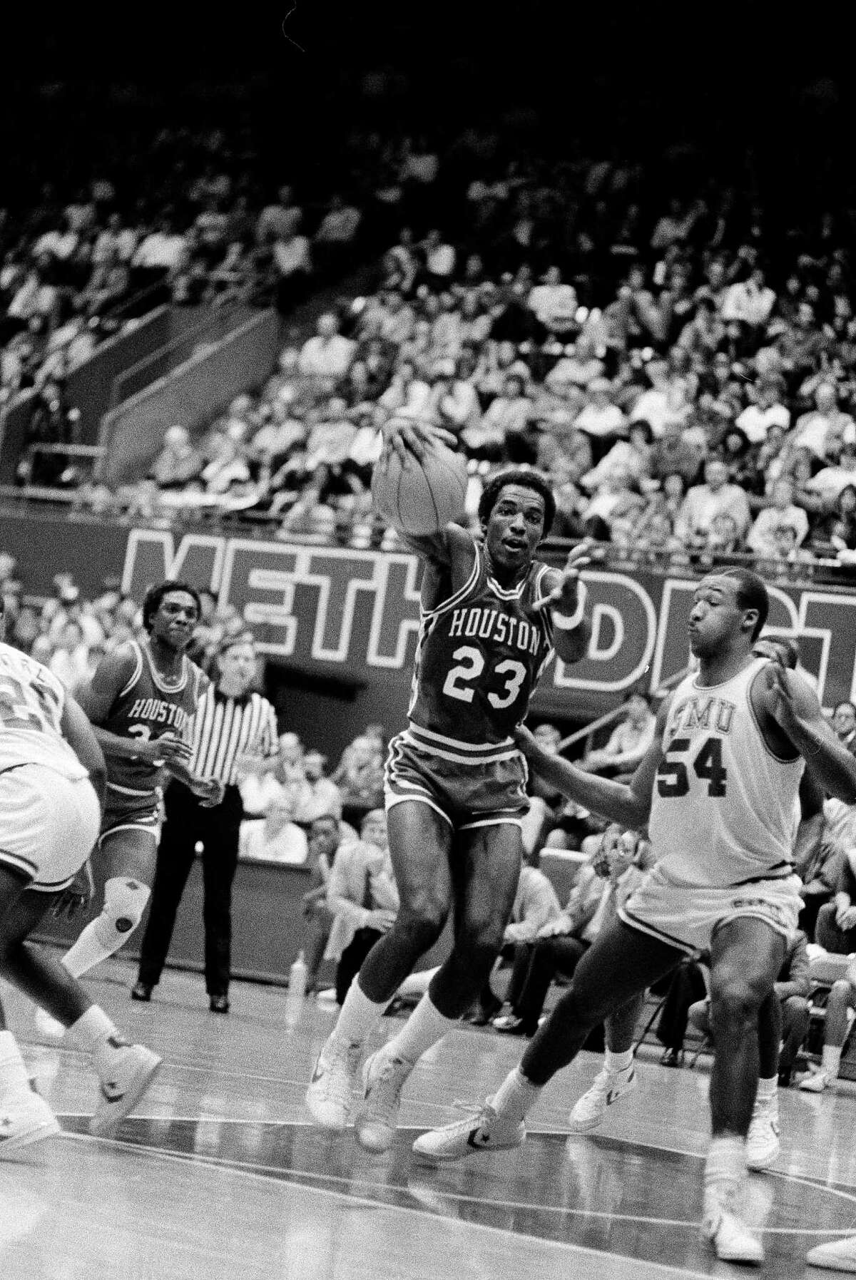 University of Houston's Clyde Drexler (23) loses control of the ball as he drives past Southern Methodist University's Larry Davis (54) in the first half of Southwest Conference play in Dallas, Feb. 9, 1983. Drexler was called for a penalty on the play.