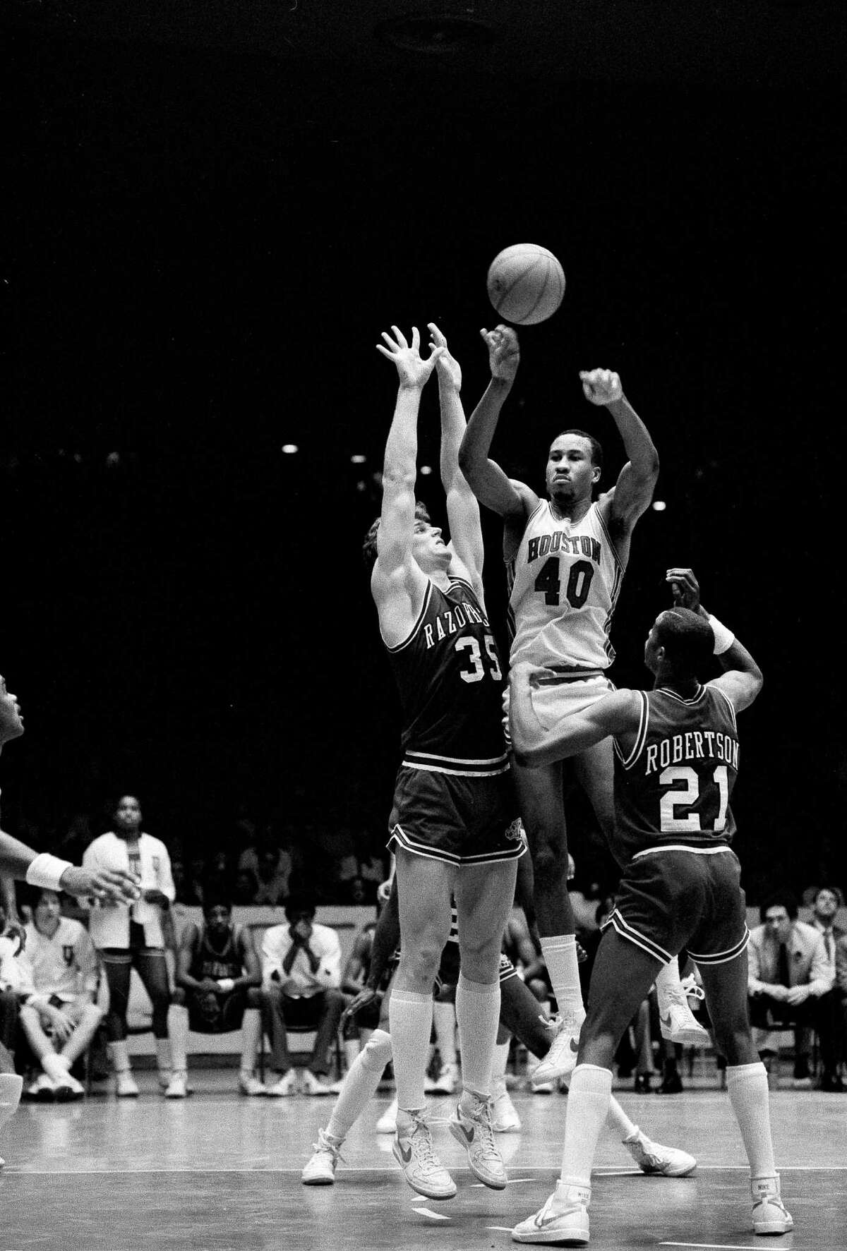 University of Houston's Larry Micheaux (40) is surrounded by Arkansas Razorbacks' Joe Klein (35) and Alvin Robertson (21) and decides to pass the ball during the first half of the Southwestern Conference in Houston, Jan. 22, 1983.