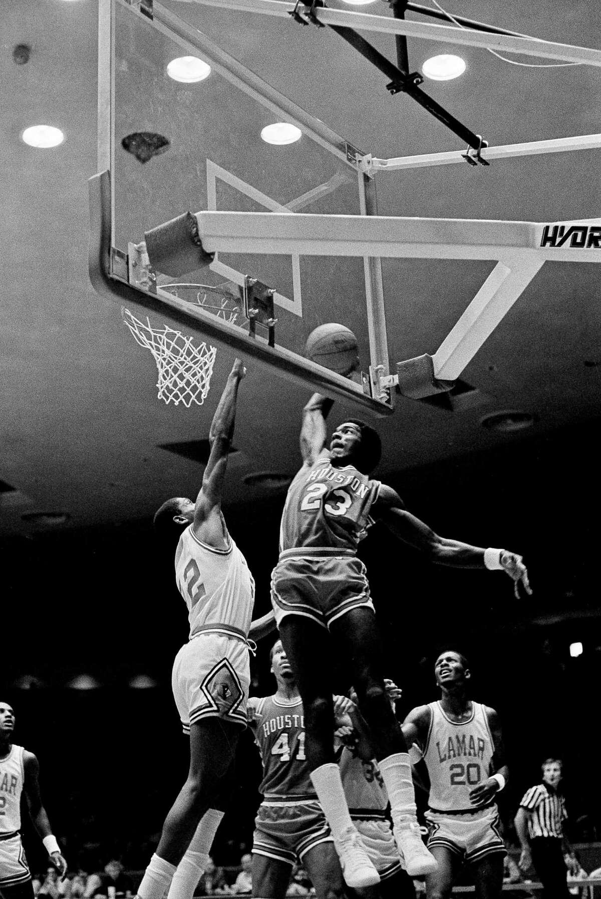 University of Houston's Clyde Drexler (23) cocks his arm for a slam dunk over the outstretched arm of Lamar University's Kenneth Cook (42) in the finals of the Kettle Classic at Hofheinz Pavilion, Houston, Nov. 28, 1982. Larry Micheaux (41) and Brian Kelleybrew (20) look on.