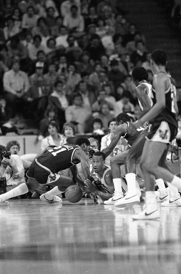 Houston center Larry Micheaux, on floor, pushes the ball to a teammate as Villanova forward Harold Pressley (21) dives for the loose ball in the second half of NCAA Midwest Regional championship game in Kansas City, March 27, 1983. Photo: Doug Atkins, Associated Press File Photo / 1983 AP