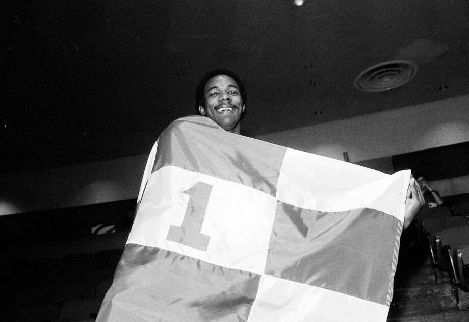 University of Houston's Clyde Drexler wraps himself in the Number One flag after learning they were on top of the Associated Press College Basketball poll, Houston, Feb. 28, 1983. Photo: Ed Kolenovsky, Associated Press File Photo / AP1983