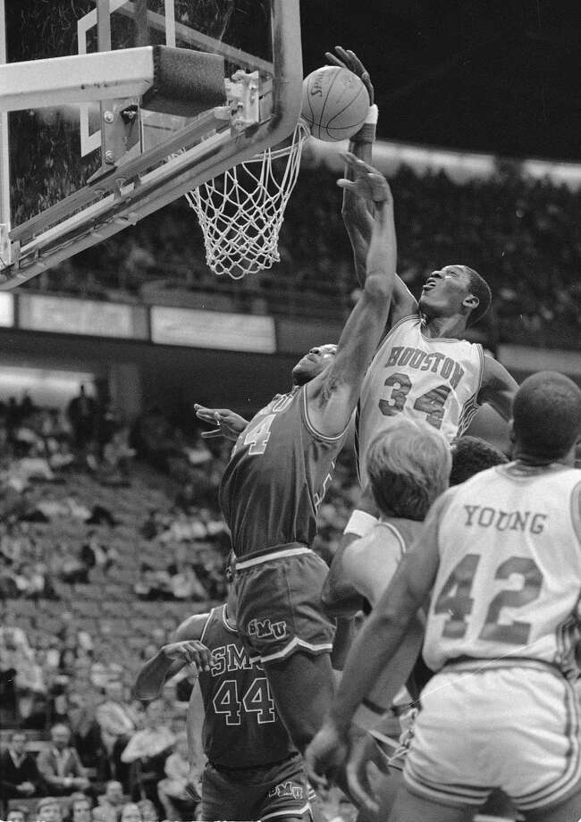 University of Houston's Akeem Abdul Olajuwon (34) goes above the rim to pull down a rebound against Southern Methodist Unviersity's Larry Davis (54) during the first period of their game in the Southwest Conference Tournament in Dallas, March 11, 1983. Photo: Ron Heflin, Associated Press File Photo / AP1983