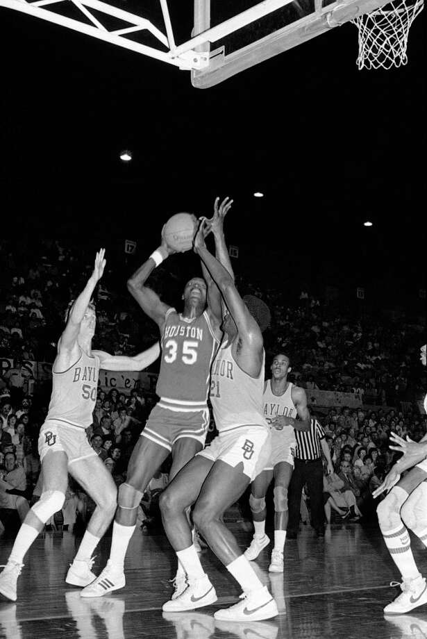 University of Houston center Akeem Abdul Olajuwon (34) looks for an opening during the first period to make a shot against Baylor University in Waco, Texas on March 5, 1983. Closing in on Olajuwon is Baylor's forward David Cover (50) and center Ozell Hall (21). Photo: Associated Press File Photo