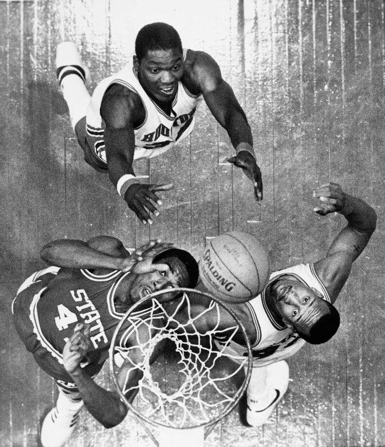 North Carolina State's Thurl Bailey (41), Houston's Akeem Abdul Olajuwon, rear, and Houston's Larry Micheaux, right, go for the rebound during NCAA game Monday night, April 4, 1983 in Albuquerque, N.M. Photo: STF, Associated Press File Photo / AP2006