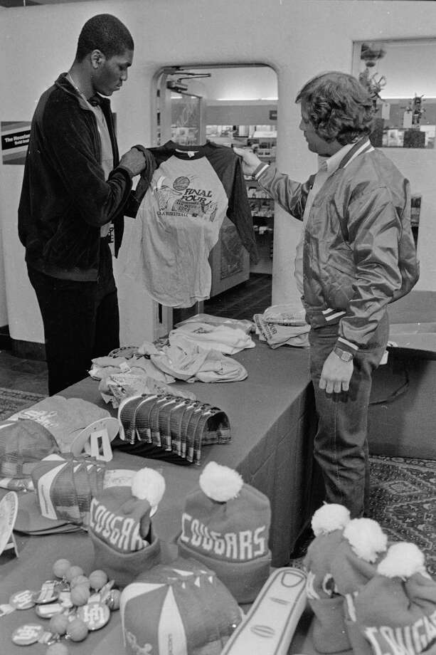 University of Houston's Akeem Abdul Olajuwon looks over a shirt being sold by souvenir vendor Mike Dannelley, in Albuquerque, N.M., after attending a press conference, April 4, 1983. Photo: Associated Press File Photo