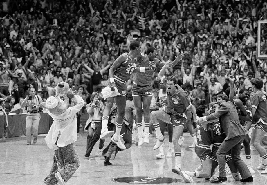 A high jumping Cozell McQueen, 45, left, leads his team airborne in a jubilant moment as others embrace in victory following the North Carolina State win over Houston on April 4, 1983 in Albuquerque. Photo: Anonymous, Associated Press File Photo / AP1983
